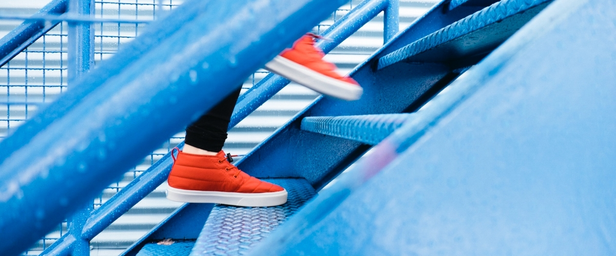 entrepreneur wearing orange shoes walking up blue stairs