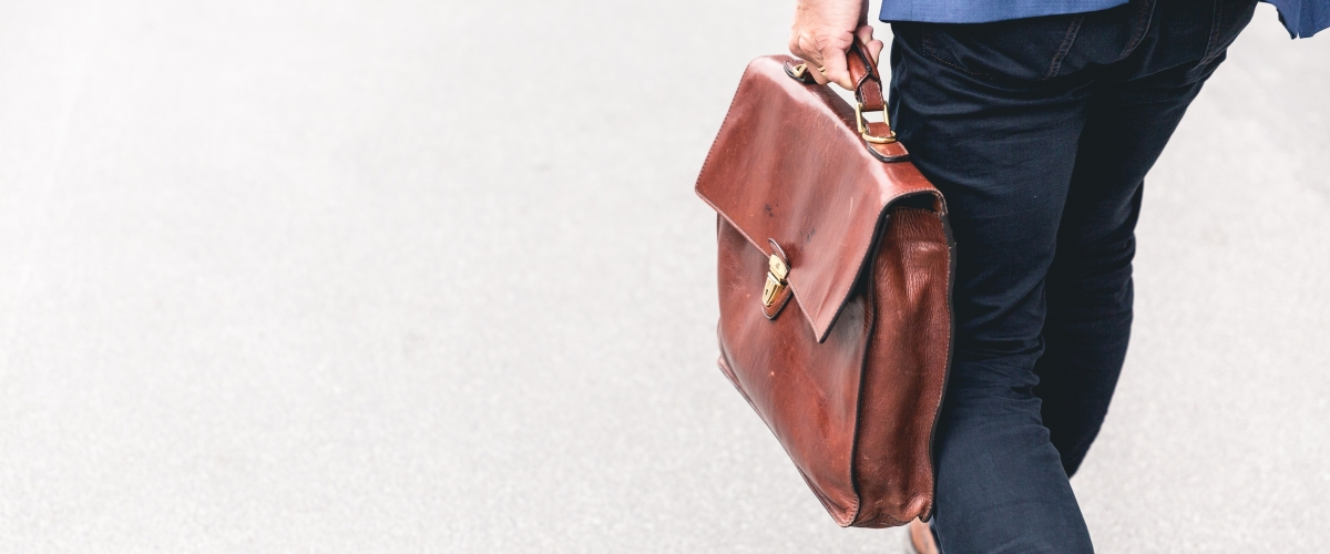 Walking businessman holding a leather briefcase