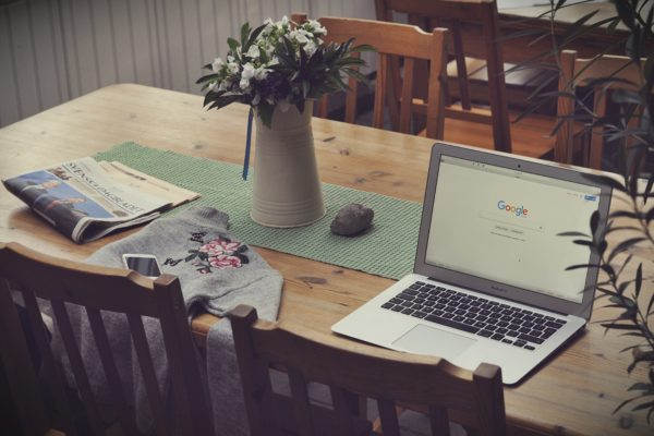 Kitchen table with a laptop that has google open