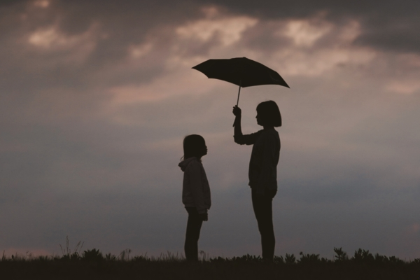 Girl silhouetted holding an umbrella for another girl