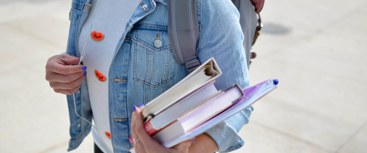 First year college student carrying books