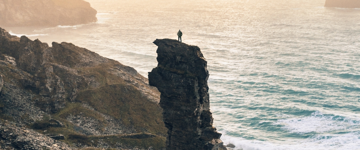 person standing on a cliff surrounded by water