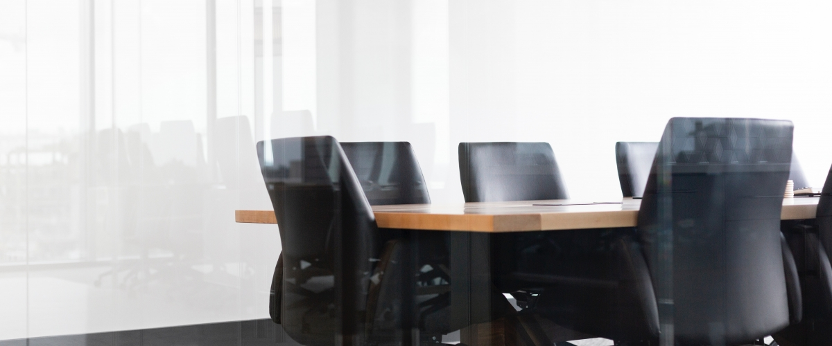 Empty office chairs around a table in a meeting room