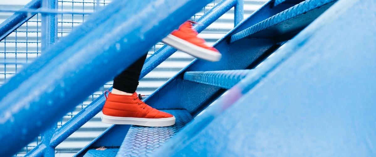 entrepreneur wearing orange shoes walking up blue stairs