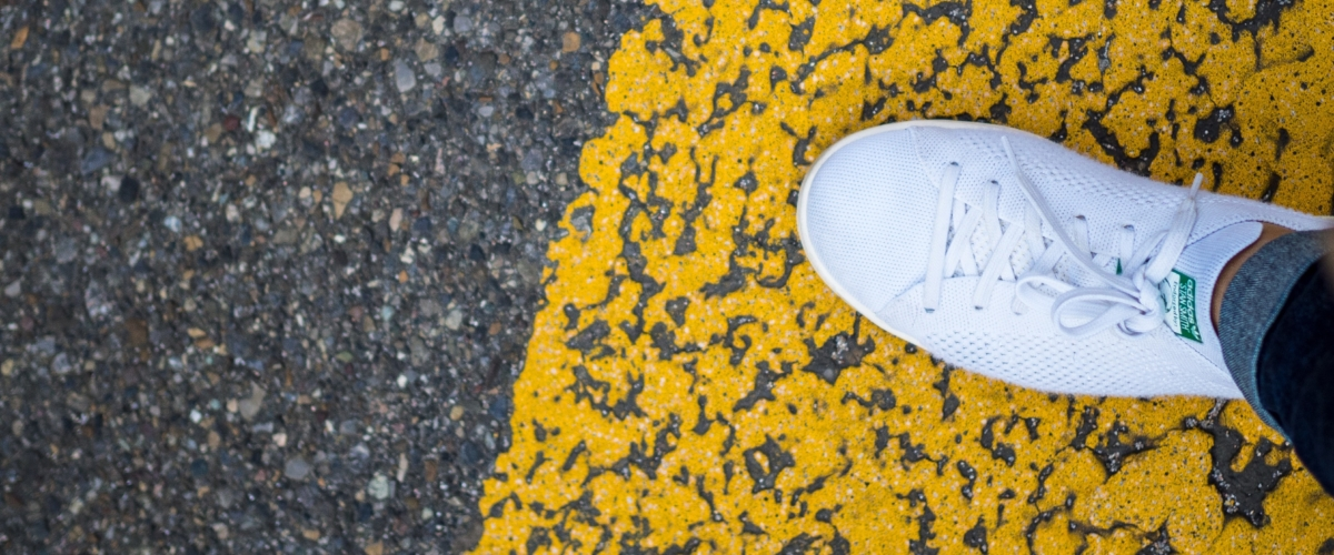 Person wearing a white shoe on the road