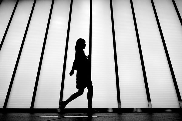 Silhouette woman walking on a white background going the extra mile