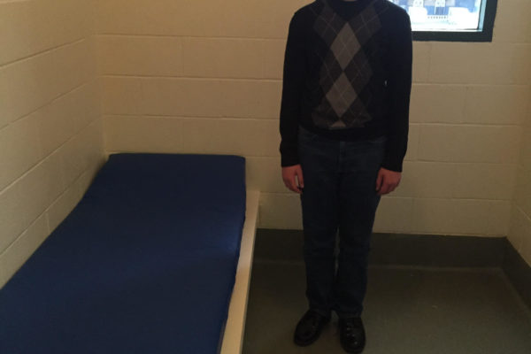 Curtis Zimmerman's son standing in a jail cell