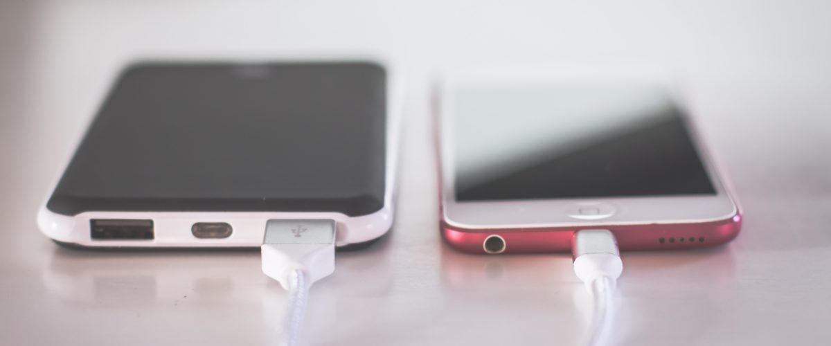 Two charging phones sitting on a table