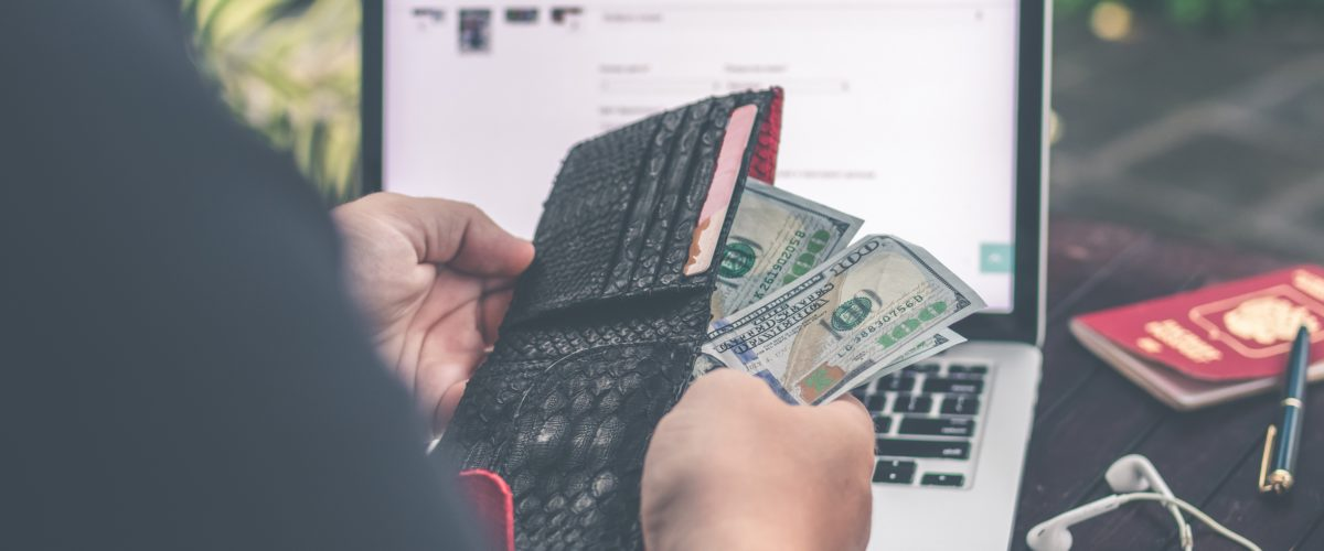 Employee on his laptop opening a wallet and taking out money