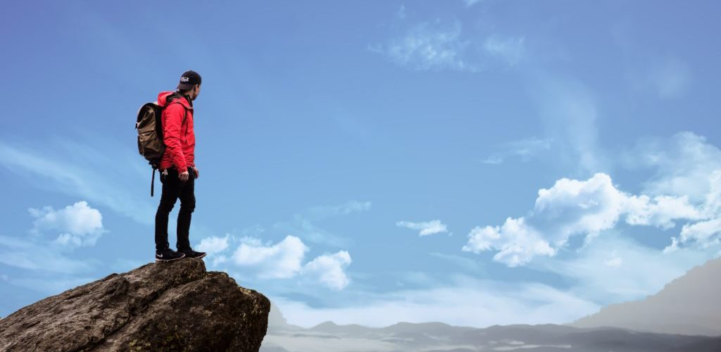 Adult standing on a mountain thinking about life