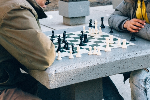 Two people playing chess in the park