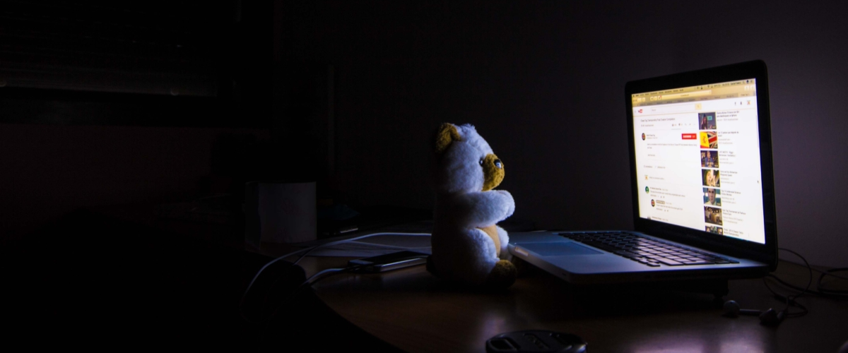 Laptop lighting up a room with a teddy bear on the keyboard