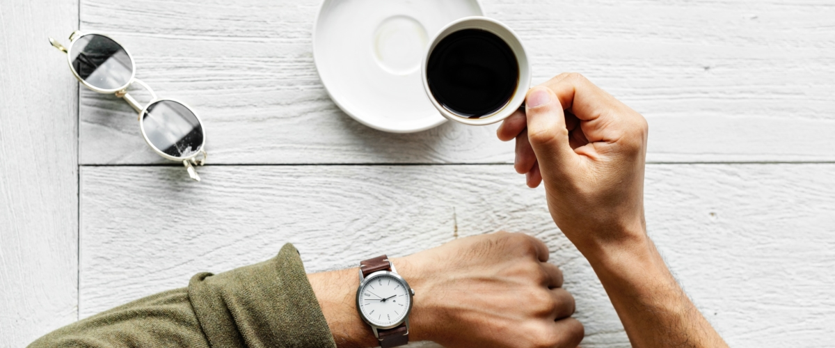 Motivated entepreneur drinking coffee and looking at watch