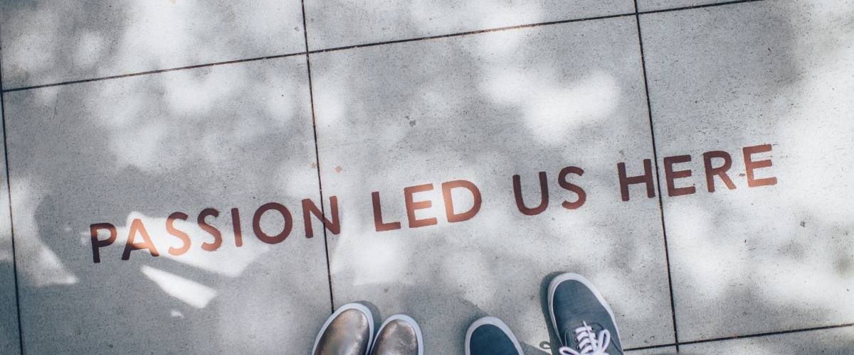 two pairs of feet standing on a sidewalk alongside the words 'passion led us here'